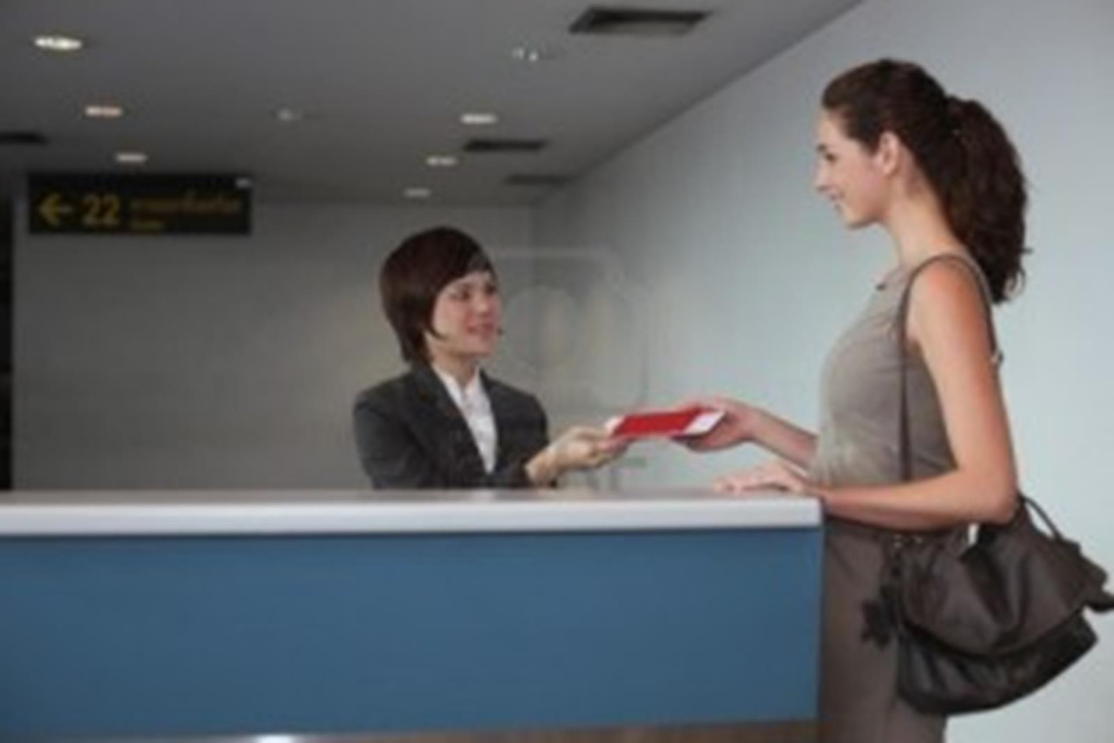 11543786-airline-check-in-attendant-returning-businesswoman-s-passport-at-the-airport-check-in-counter