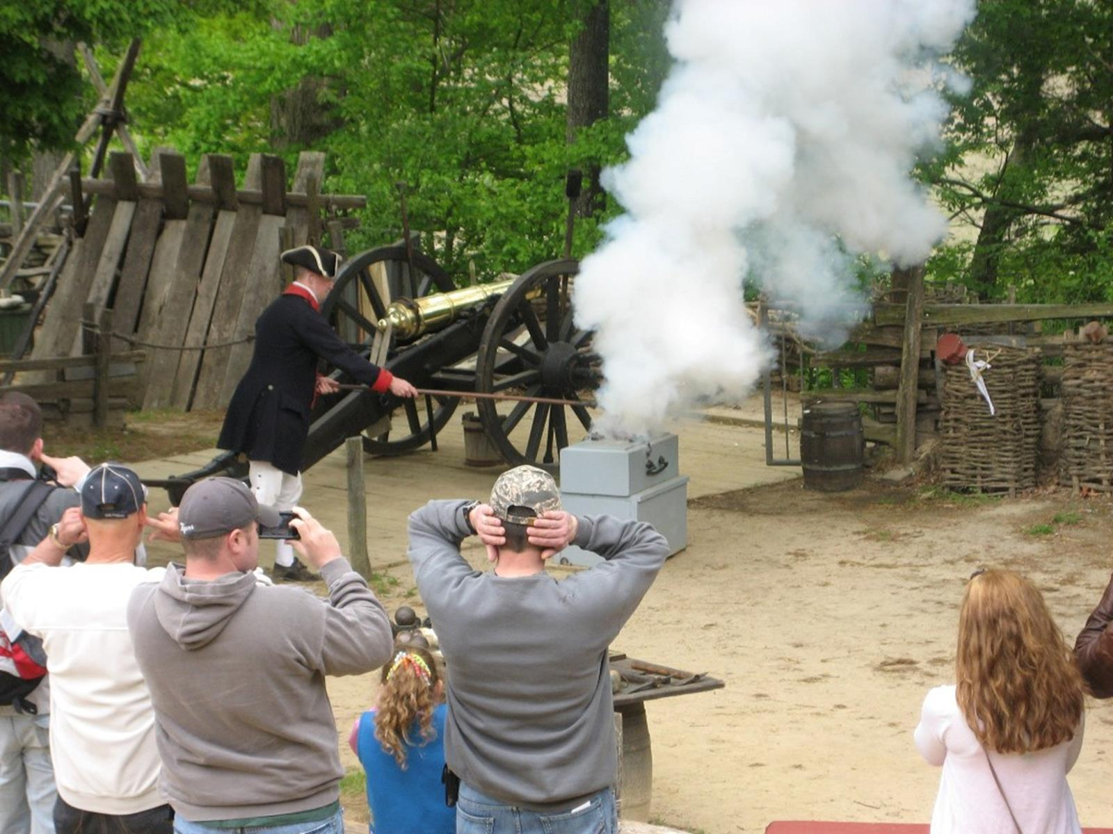 Visitors cover their ears as a mortar is fired in the Yorktown Victory Center's re-created Continental Army encampment. Credit: the Jamestown-Yorktown Foundation.