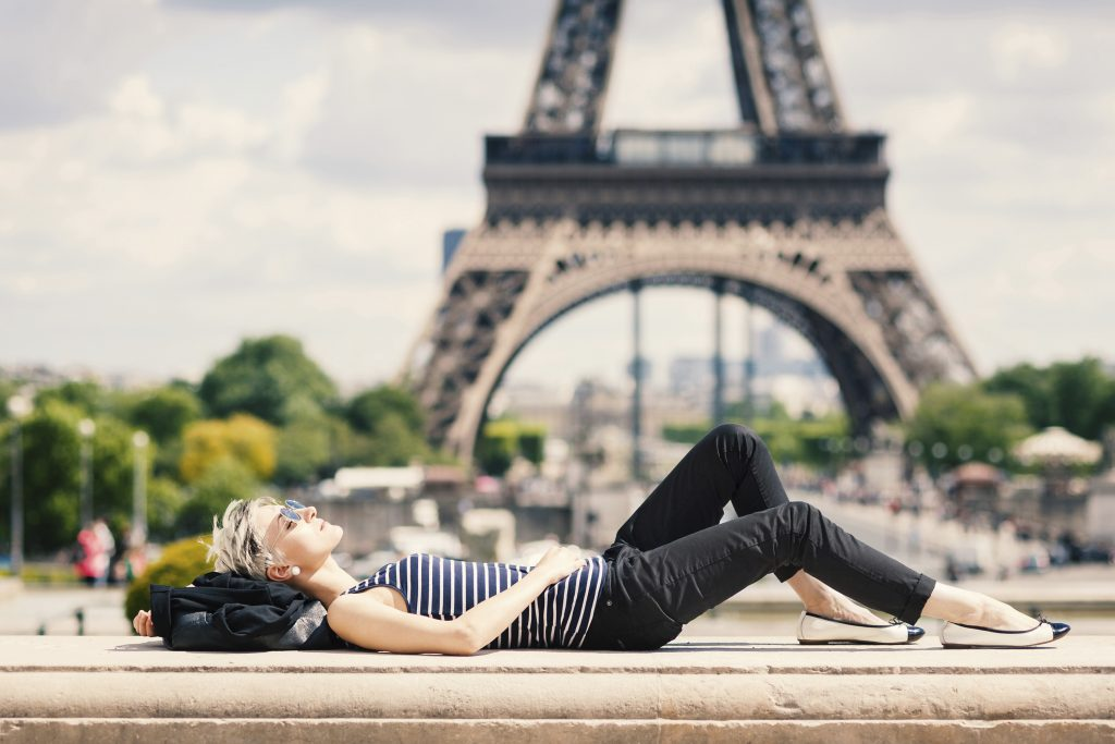 Relaxed young blonde woman portrait laying on the ground.