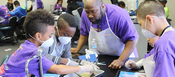 Elementary school and middle school boys and girls participate in STEM workshops.